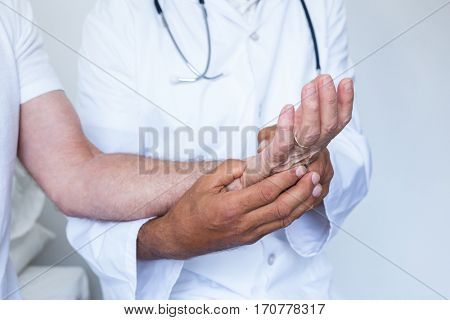 Male doctor giving palm acupressure treatment to the patient in hospital