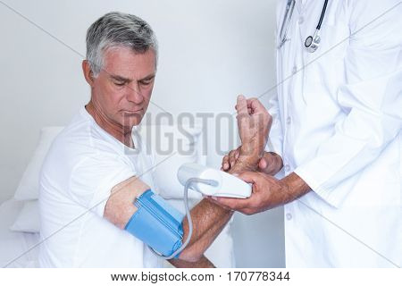 Doctor checking senior mans blood pressure in hospital