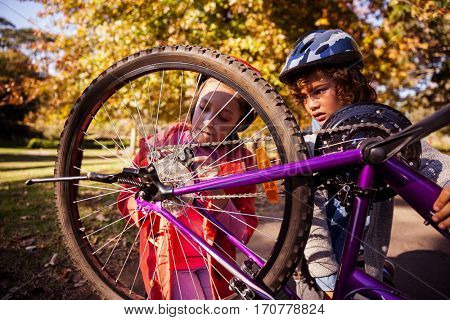 Concentrated siblings repairing mountain bike in park