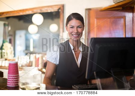 Waitress working on computer at counter in a restaurant