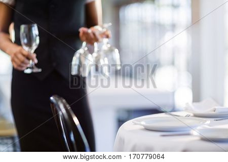 Mid section of waitress setting the table in restaurant