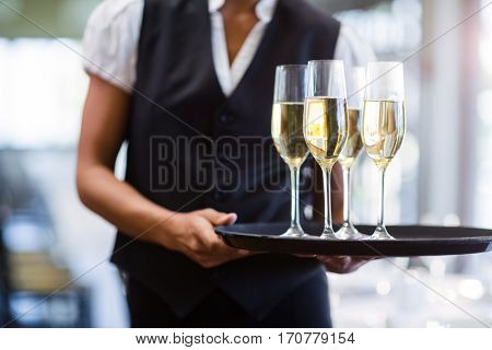 Waitress holding serving tray with champagne flutes in restaurant