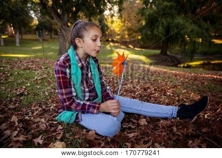 Girl blowing pinwheel while sitting in park during autumn