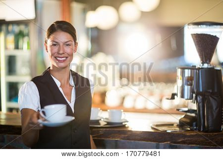 Portrait of smiling waitress serving cup of coffee in restaurant