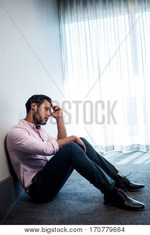 Upset businessman sitting against the wall in studio