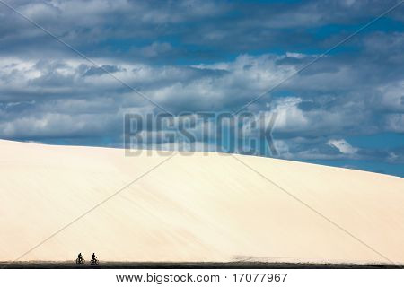 tourist doing bicycle at the bottom of the big sand dune  on the beach of the beautiful fisherman village of Jericoacoara in ceara state brazil