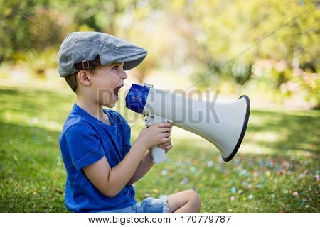 Young boy speaking on megaphone in park