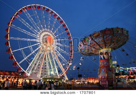 Carnival giant wheel and wave swinger at the dusk poster