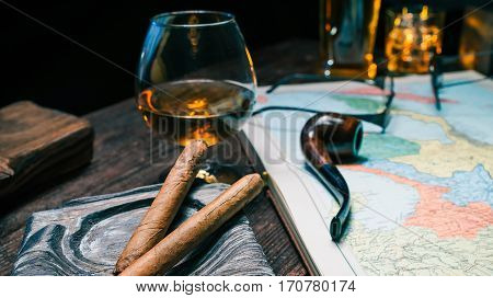 Close-up view of travellers desk. Old map atlas, cigar and tobacco pipe and brandy