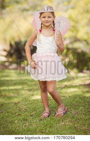 Portrait of young girl pretending to be a fairy in park