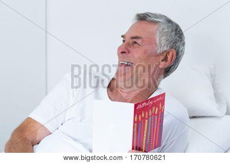Happy of senior man holding birthday greeting card