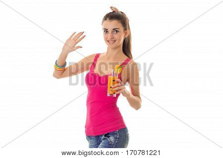 cutie young brunette girl in light summer clothes with orange cocktail in her hands looking at the camera and smiling isolated on white