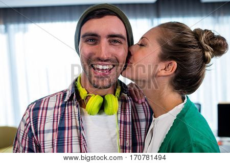 Woman worker kissing her colleague in office