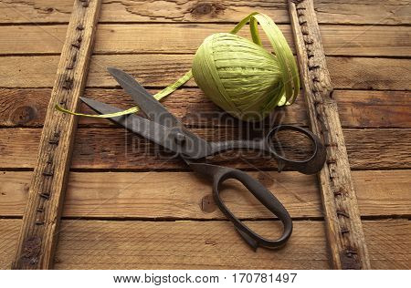 Vintage Background with sewing tools/Sewing kit. Scissors bobbins with thread on the old wooden background