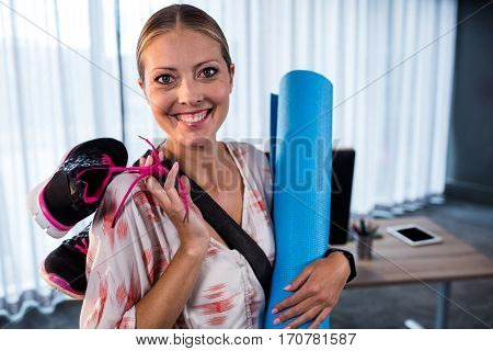 Casual businesswoman with yoga mat and sports shoes in the office