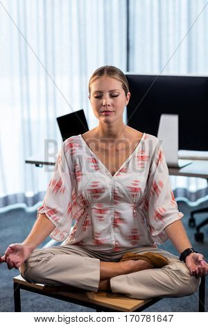 Portrait of businesswoman doing yoga at the office
