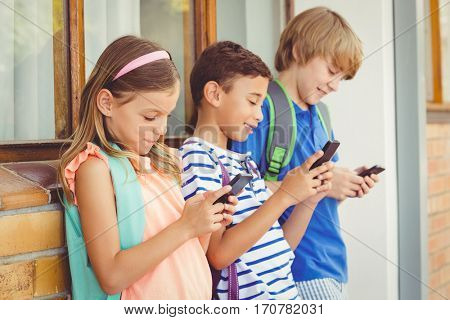 School kids standing in corridor and using mobile phone at school