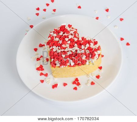 Pile of pancakes in the shape of a heart on white plate with little white and red sugar hearts