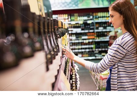 Young woman selecting wine in the supermarket