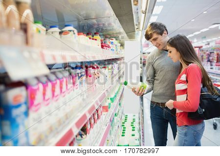 A serious couple buying products at grocery store