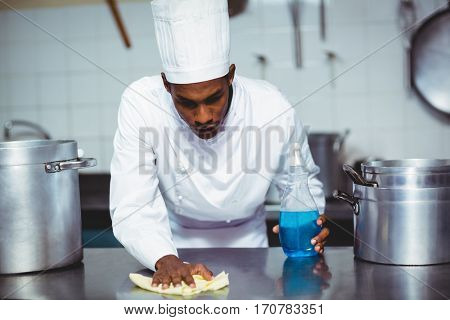 Chef cleaning kitchen counter with a bottle of solution and a rag