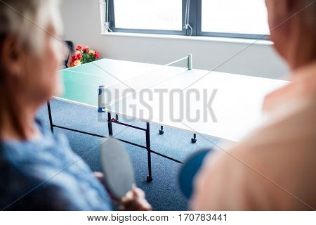 Two seniors front of a ping pong table in the retirement house