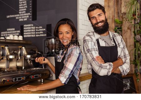 Portrait of two waiters with a coffee machine in the bar