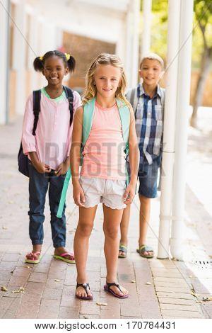 Portrait of smiling school kids standing in school corridor
