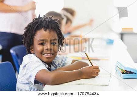 Portrait of school boy doing homework in classroom at school