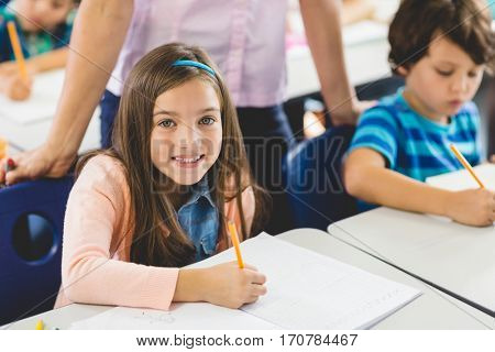 School girl doing homework in classroom at school