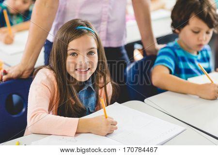 School girl doing homework in classroom at school poster