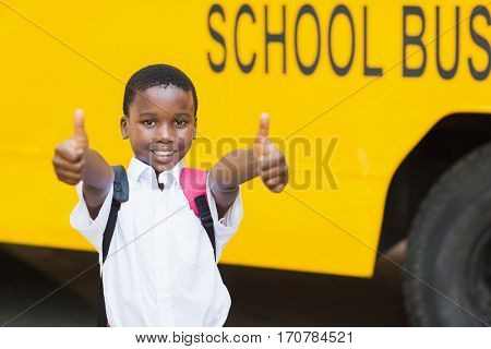 Portrait of smiling schoolboy showing thumbs up in front of school bus