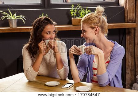 Smiling friends drinking coffee in the cafe