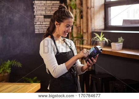 Smiling waitress using a bank card reader in cafeteria
