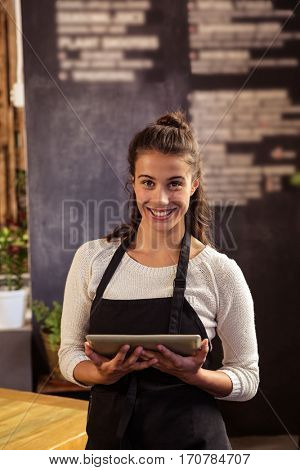 Portrait of beautiful waitress standing with digital tablet in cafeteria