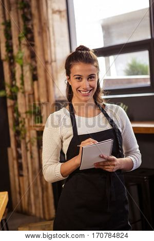 Portrait of beautiful waitress taking order in cafeteria