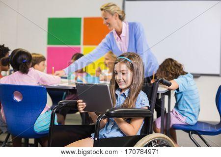Disabled schoolgirl using digital tablet in classroom at school