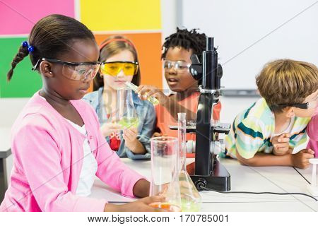 Kids doing a chemical experiment in laboratory at school