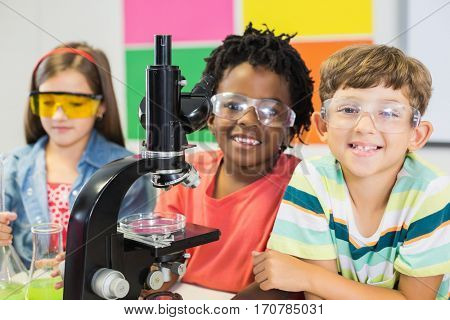 Kids doing experiment on microscope in laboratory at school