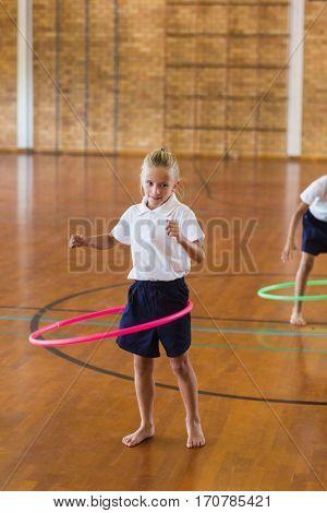 Schoolgirl playing with hula hoop in school gym at elementary school