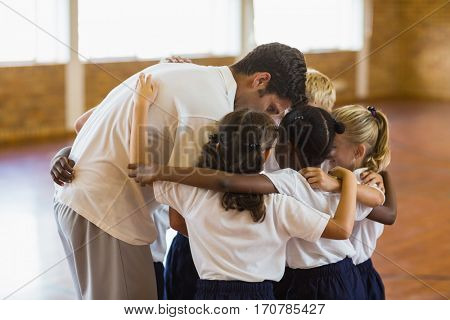 Sport teacher and students forming a huddle in school gym