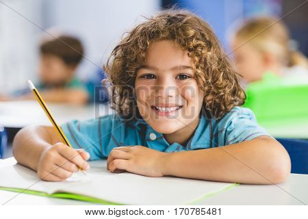 Portrait of smiling schoolboy studying in classroom at elementary school
