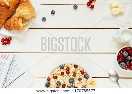 Healthy breakfast with oat flakes, berries, croissants on the white wooden table with copy space, top view.