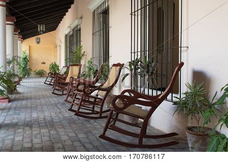 Central backyard typical of old Spanish colonial houses. The are a row of rocking chairs. Cuba is famous for the preservation of historic buildings from its past.