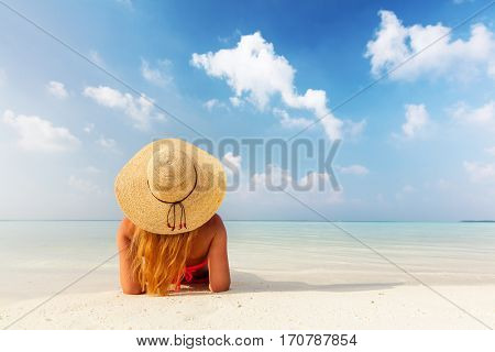 Beautiful young woman in sunhat lying relaxed on sand, tropical beach in Maldives