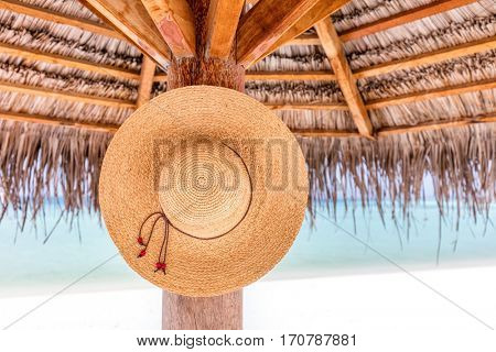 Sun hat hanging on sunshade umbrella on tropical beach. Indian Ocean, Maldives.