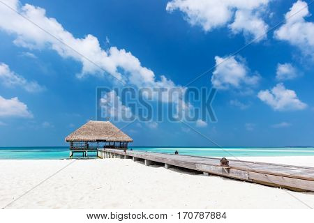 Maldives islands resort on Indian Ocean. Wooden jetty with water relaxation lodge.