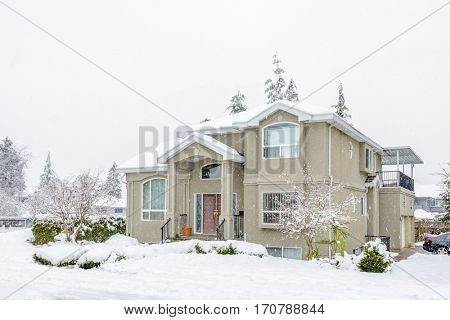 A heavy snowfall. The typical american house in winter. Snow covered.