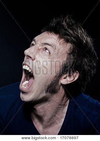 studio portrait on black background of a funny expressive caucasian man screamin