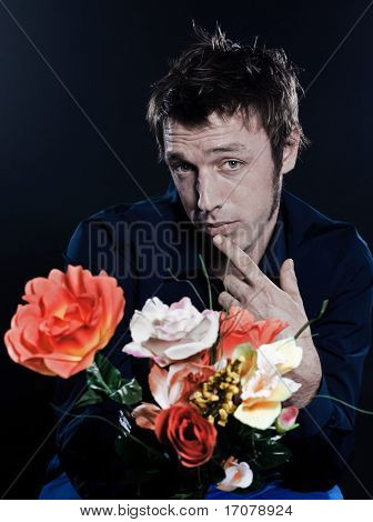 studio portrait on black background of a funny expressive caucasian man offering flowers sh
